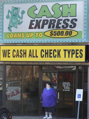In this file photo, Jennifer Trogdon walks out of Cash Express near the intersection of National Avenue and Battlefield Road after making a payment on a payday loan.