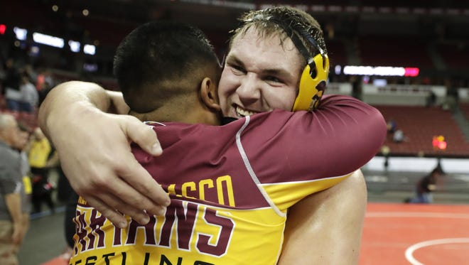 Luxemburg-Casco senior Phil Rasmussen hugs his coach George Jimenez after his 285-pound WIAA Division 2 semifinal win at the WIAA individual state wrestling tournament.