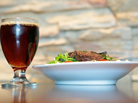 A glass of the Bin 1214 rounded red ale is photographed with the angus flat iron steak salad at Babe's Bar-B-Que & Brewhouse at The River in Rancho Mirage on Monday, February 23, 2015. The seasonal beer features a blend of cherries, blackberries as well as French and American Oak.