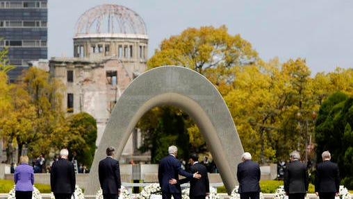 FILE - In this April 11, 2016, file photo, U.S. Secretary of State John Kerry, fourth from left, puts his arm around Japanese Foreign Minister Fumio Kishida after they and fellow G7 foreign ministers laid wreaths at the cenotaph at Hiroshima Peace Memorial Park in Hiroshima, western Japan. U.S. President Barack Obama will travel to Hiroshima in May 2016 in the first visit by a sitting American president to the site where the U.S. dropped an atomic bomb. Obama's visit will bolster his call for denuclearization and honor victims of the bombing that killed 140,000 Japanese on Aug. 6, 1945. The president's visit had long been anticipated. (Jonathan Ernst/Pool Photo via AP, File)