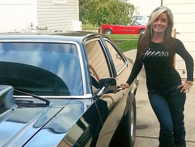 Jessica Tackett, 25, poses next to a muscle car. The