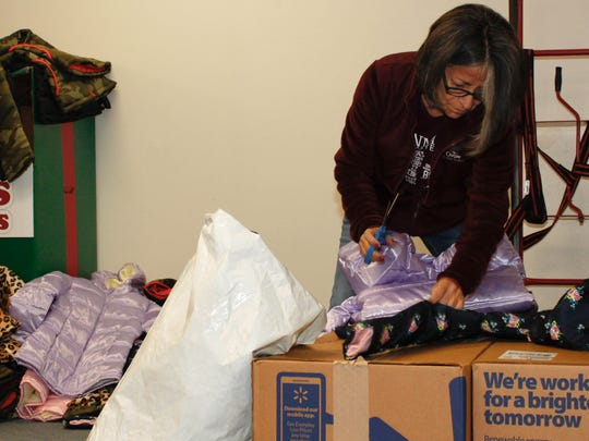 Community Action Agency of Southern New Mexico volunteer Elisa West unpacks coats that have been donated to the organization.
