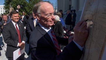 Alabama Governor Robert Bentley, right, signs a map of the state of Alabama as Sen Arthur Orr, left, looks on after the discussed plans for Alabama's bicentennial celebration at a press conference on the steps of the Alabama Capitol Building in Montgomery, Ala. on Friday March 3, 2017.