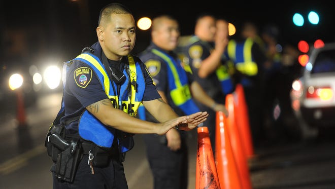 In this Dec. 31, 2011 file photo, Guam Police officer L.J. Aguon directs a motorist to slow down while conducting a DUI checkpoint with fellow officers from the Highway Patrol Division in Barrigada.