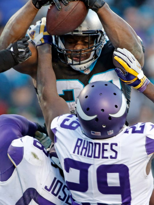Carolina Panthers' Jonathan Stewart (28) dives over the goal line against Minnesota Vikings' Xavier Rhodes (29) for a touchdown during the second half of an NFL football game in Charlotte, N.C., Sunday, Dec. 10, 2017. (AP Photo/Bob Leverone)