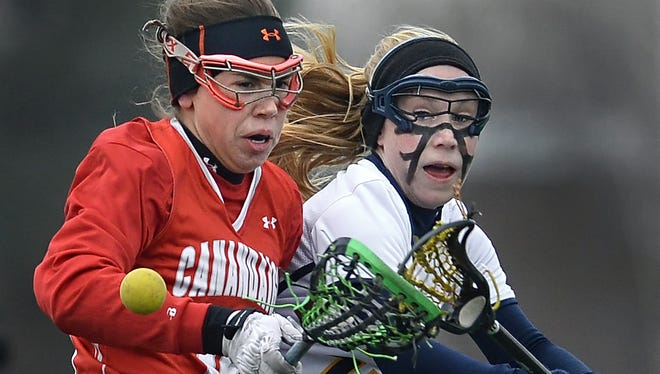 Victor's Kaci Messier, right, knocks the ball away from Canandaigua's Megan Hoffman on April 23, 2015. Victor beat Canandaigua 9-4.