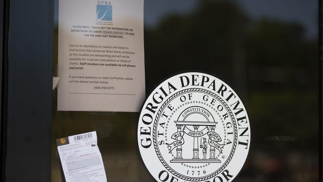 A sign posted on the locked doors of a Georgia Department of Labor office advises workers at the office are working remotely and are not available in person consultation before of the coronavirus Thursday, May 7, 2020, in Norcross Ga.