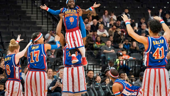 """The Harlem Globetrotters' Hot Shot Swanson is lifted in the air by """"Beast"""" Douglas during a game against the Washington Generals at the Barclays Center on December 26, 2017, in New York."""