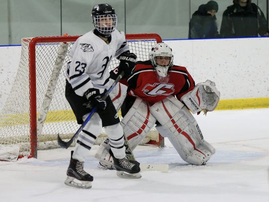 Plymouth's Gavin Roach (23) parks in front of Canton goalie Jaxon Taylor during the Dec. 27 game at Arctic Edge Arena.