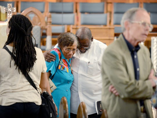 """Rev. Mary Frances Grant, left, and Pastor Spencer Hardaway, of Rock Hill Missionary Baptist Church, talk and hug following an afternoon prayer vigil for the family of Jai """"Jerry"""" Williams, the man shot and killed by a police officer on Saturday, and for the City of Asheville on Wednesday, July 6, 2016. Area preachers led the group in prayer for community healing, trust and the forming of a """"love chain."""""""