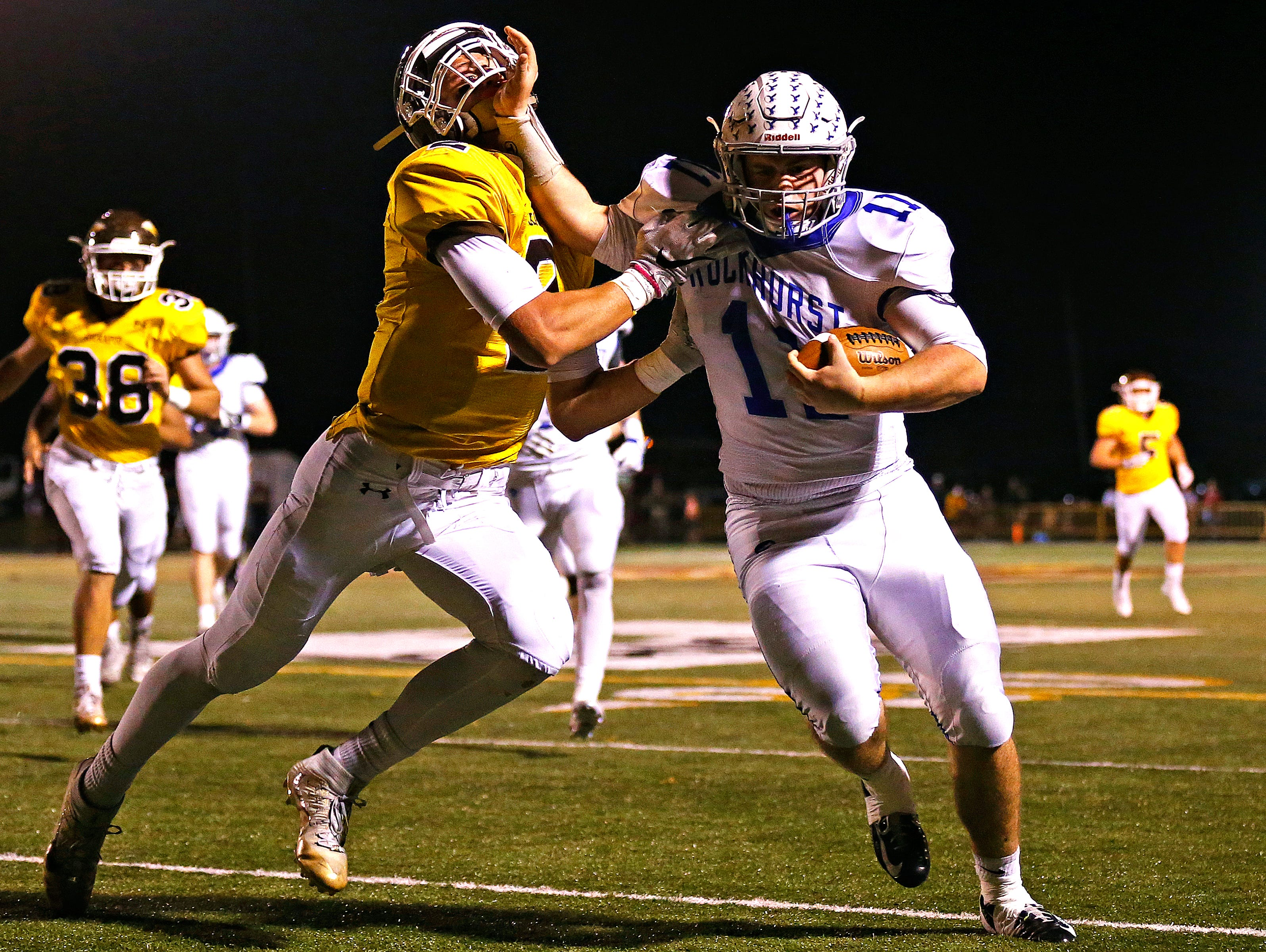 Rockhurst High School quarterback Chance May (11) stiff arms Chiefs linebacker Travis Vokolek (2) during first quarter action of the Class 6 playoff game between Rockhurst High School and Kickapoo High School played at Pottenger Stadium in Springfield, Mo. on Oct. 28, 2016.