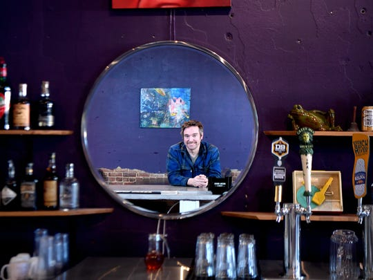 Josh Gambrell, co-owner of The Malvern in West Asheville, is reflected in the mirror of the bar, for a portrait on Wednesday, Nov. 29, 2017.