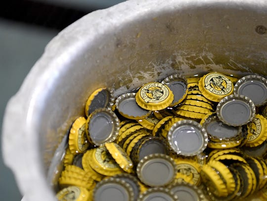 Bottle caps sit in water before being used to cap Imperial
