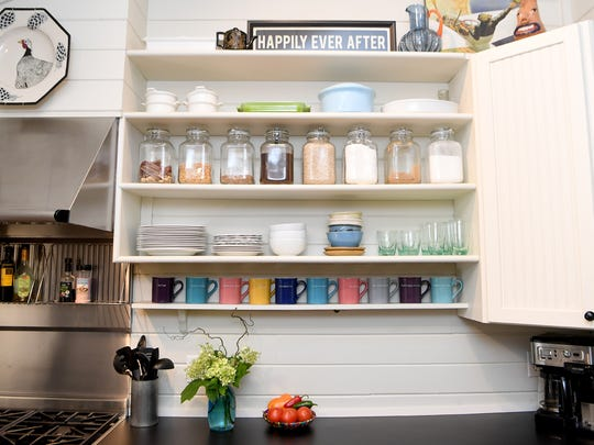 The kitchen of Jeff Wilke and Jenny Gray's home in Deerhaven is small but the space is used effectively with jars to hold ingredients on the open shelves giving the space a country kitchen feel.