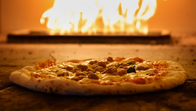 A pizza cooks in the oven Wednesday, April 6, at Pompeii Pizzeria in Elk River.
