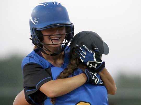 Martensdale-St. Marys' Hannah Sweet gets a hug from Kaitlyn Schad after MSM rallied to win a regional final.