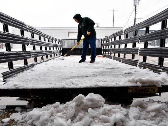 Cody Barr of Morrison Supply uses a rake to scrape the ice out of a flat-bottom truck Thursday. Drizzle and cloudy skies started the day with temperatures hovering at, or slightly below, freezing all day.