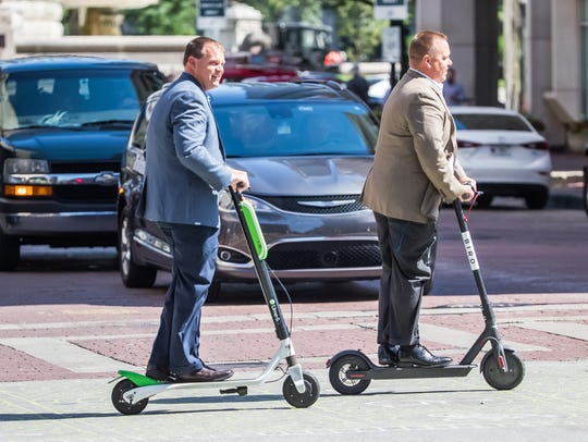 Lime and Bird scooter riders travel along downtown