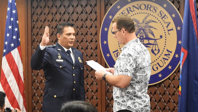 Vince San Nicolas Perez, left, takes an oath as the new chief of Guam Customs and Quarantine Agency during his pinning ceremony in the Ricardo J. Bordallo Governor's Complex at Adelup on June 28, 2017. Lt. Gov. Ray Tenorio administered the oath as Perez's friends, family and fellow Customs officers watched.