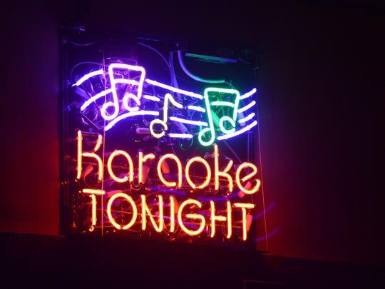 A neon sign promoting karaoke night hangs in the Orange Carpet in downtown Lancaster.