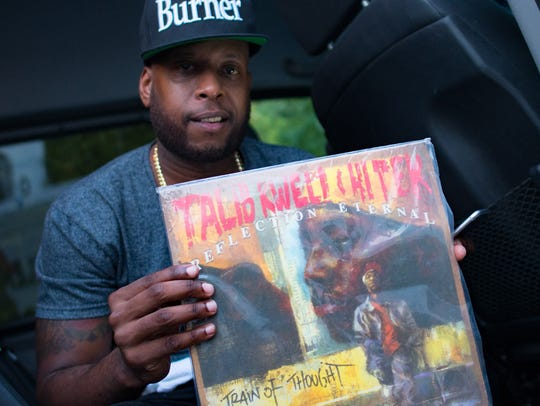 Talib Kweli with a copy of one of his own albums at