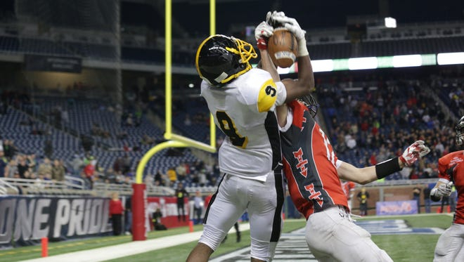 Detroit Martin Luther King Donnie Corley catches the game-winning touchdown against Lowell Gabe Steed, during the Michigan High School Athletic Association football finals at Ford Field in Detroit on Friday, Nov. 27, 2015. King won 40-38.