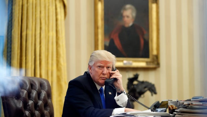 President Donald Trump speaks on the phone in the Oval Office of the White House, with a portrait of Andrew Jackson in the background. All Tennessee lawmakers are invited to hear Trump speak at the Hermitage, Jackson's home outside downtown Nashville, Wednesday afternoon.