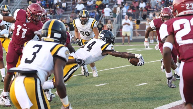Neville's DeMaine Riley (4) stretches the ball across the goal line for a touchdown. The Tigers rushed for 247 yards in a 23-14 win over Ouachita.