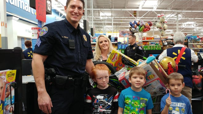 Mesquite Police Sgt. Christopher Rowley, left, who led this year's Shop with a Cop event, stands with three local students inside Walmart.
