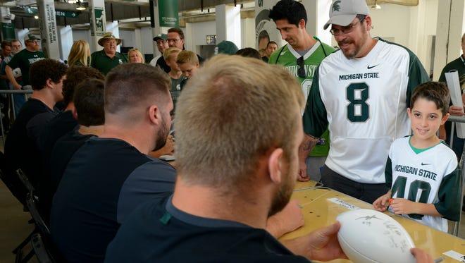 Brendan Gallardo, 9, of Temperance smiles as MSU's Brian Allen prepares to autograph his football. Next to Gallardo is his dad Ryan.