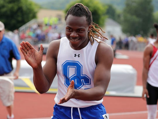 Cornelius Bright of Oak Creek is all smiles after running the fastest time in qualifying for the boys Division 1 100 meters on Friday.