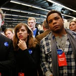 People at a Hillary Clinton event watch as results are displayed on a television during caucus night Feb.1, 2016, in Des Moines.