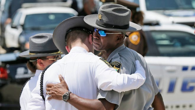 Law enforcement officers comfort each other July 13, 2016, after the funeral services for Dallas Police Sr. Cpl. Lorne Ahrens at Prestonwood Baptist Church in Plano, Texas. Ahrens and four other officers were slain by a sniper during a protest last week in downtown Dallas.