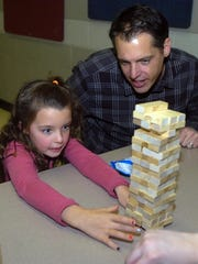 Bob Marsh watches as his daughter Harper remove a block from the Jenga structure.