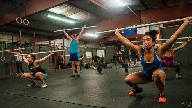 Women stretch and warm up at the start of a class at CrossFit Las Cruces.