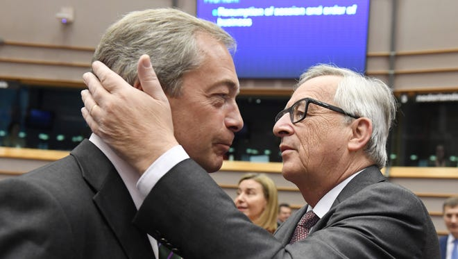European Commission President Jean-Claude Juncker, right, greets UKIP leader Nigel Farage during a special session of European Parliament in Brussels on Tuesday, June 28, 2016.