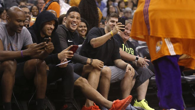 Suns star Devin Booker laughs as the Mercury mascot tries to get him to dance during the first half at Talking Stick Resort Arena in Phoenix, Ariz. on August 24, 2017.