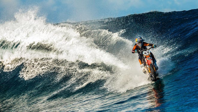 In this April, 2015, photo provided by DC Shoes, daredevil Robbie Maddison in his latest stunt rides his motorcycle across waves in Tahiti, French Polynesia, using ski-like devices on his wheels. (Garth Milan/DC Shoes via AP)