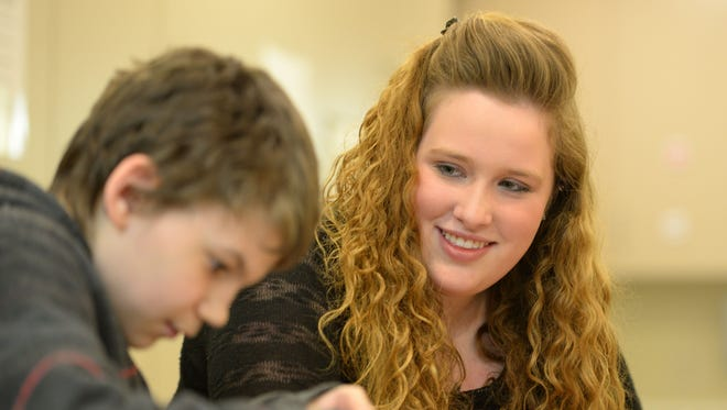 Seymour High School Academic Team member Cassandra Peters tutors a younger student in life skills.
