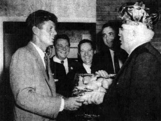 Kennedy receives a crate of yams from the  1956 Yambilee King.