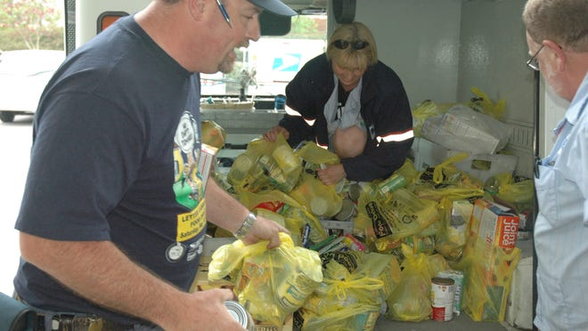 Salem-area letter carriers (from left) Tony Christensen, Kim Nickerson and Rick Miller unload donated food at a post office facility on Claxter Road NE in 2007.