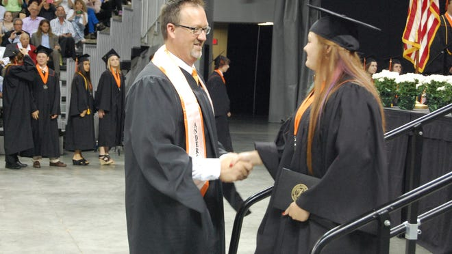 Anderson High School Principal Mike Broadwater, center, congratulates a graduating senior during a recent ceremony. Broadwater has been appointed as a new assistant superintendent for the district.