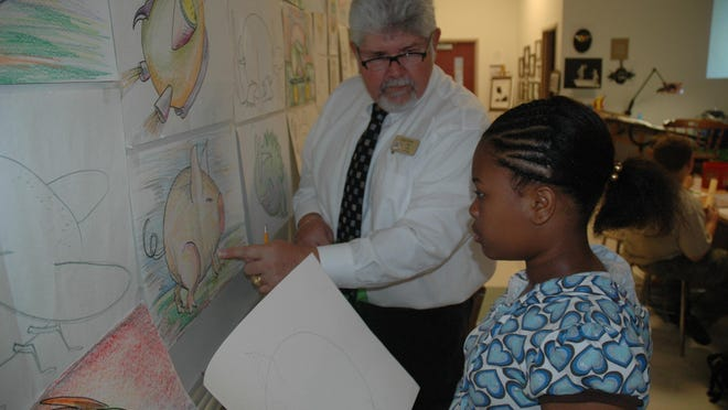 Patriot Elementary School art teacher Chad Lyons helps a student form an idea for her project. Lyons is retiring at the end of this school year after 43 years in the classroom.