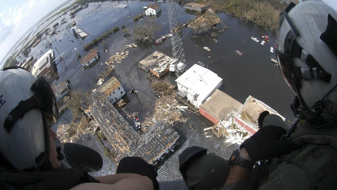 In this photo released by the Department of Defense on Sept. 1, 2005, military search and rescue crewmembers observe a rescue in progress along the Louisiana coast Wednesday, Aug. 31, 2005, as they wait to assist.