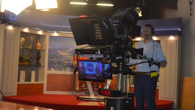 A cameraman captures a segment featuring students with the Digital Arts Technology Academy.