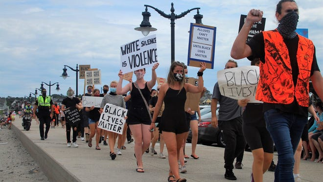 Protesters march Sunday, Aug. 2, 2020, along Short Sands beach boardwalk to call attention to police brutality and racism. They were escorted by York Police Department officers.