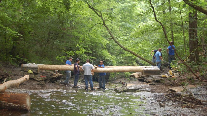 Young Hoosier Conservation Corps workers build a hiking bridge from natural materials at Clifty Falls State Park.
