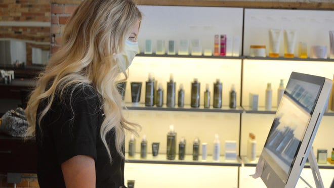 Emily Baker, brand ambassador at Engedi Salon, reviews the salon's inventory Tuesday, June 9. Salons across the state can reopen for business on Monday, June 15.