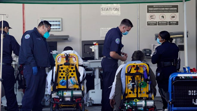 Los Angeles County emergency medical technicians deliver patients for admission at the Ambulatory Care Center station at the MLK Community Medical Group hospital in Los Angeles on Wednesday.