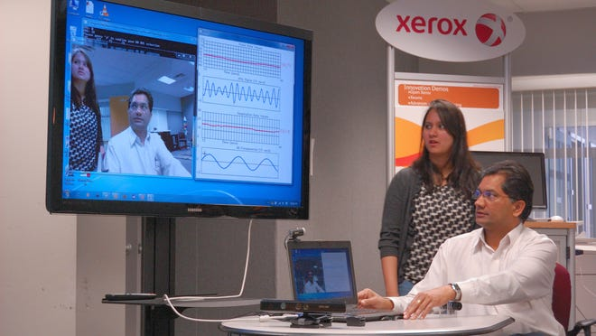Lalit K. Mestha and engineer Survi Kyal demonstrate at the Xerox Research Center in Webster how a webcam can pick up heart rates.